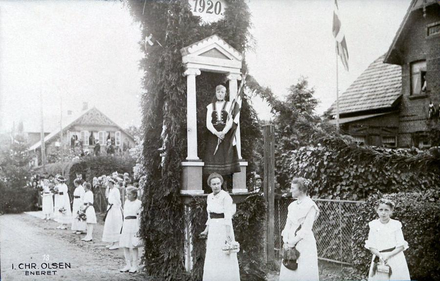 Blomsterpiger venter i siden af gaden og inde i søjlen påen æresport står en pige i fin dragt, og med Dannebrog i hånden.